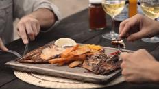 tabla con carne de pescado y cubiertos